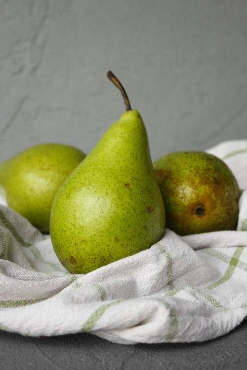 Fresh ripe green pears with brown spots placed on table on white fabric in light place near wall