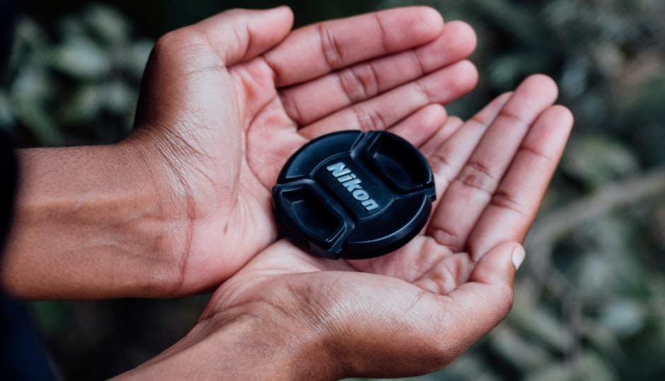 Black Nikon Camera Lens Cover on Left and Right Human Palms