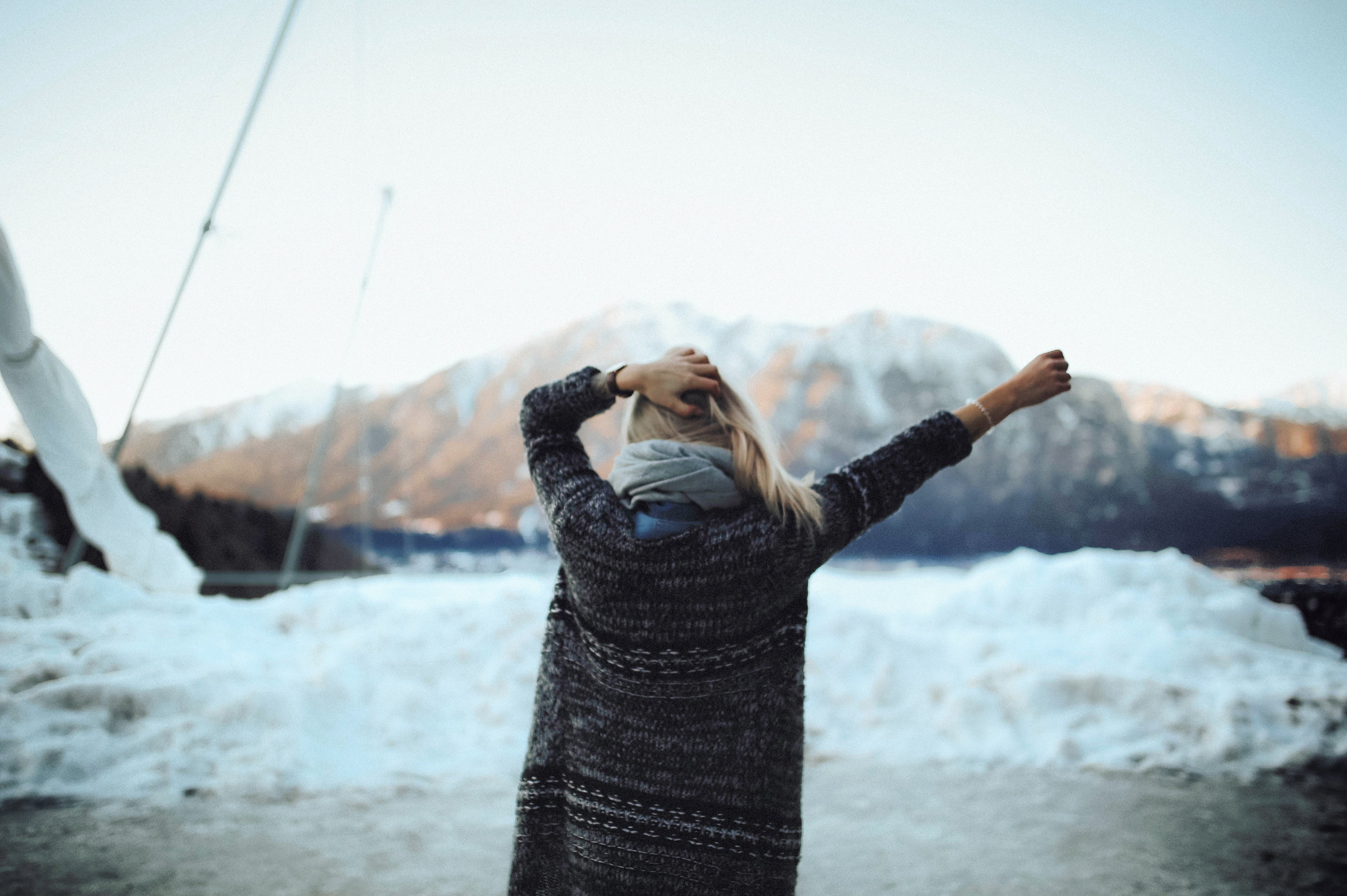 Woman in Gray and Black Tribal Cardigan Standing in Front of Snow Fields