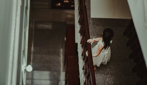 Girl in White Dress Standing in Front of Railings