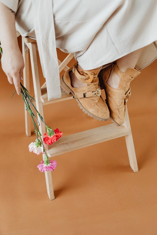 Person Wearing Brown Shoes Holding Flowers