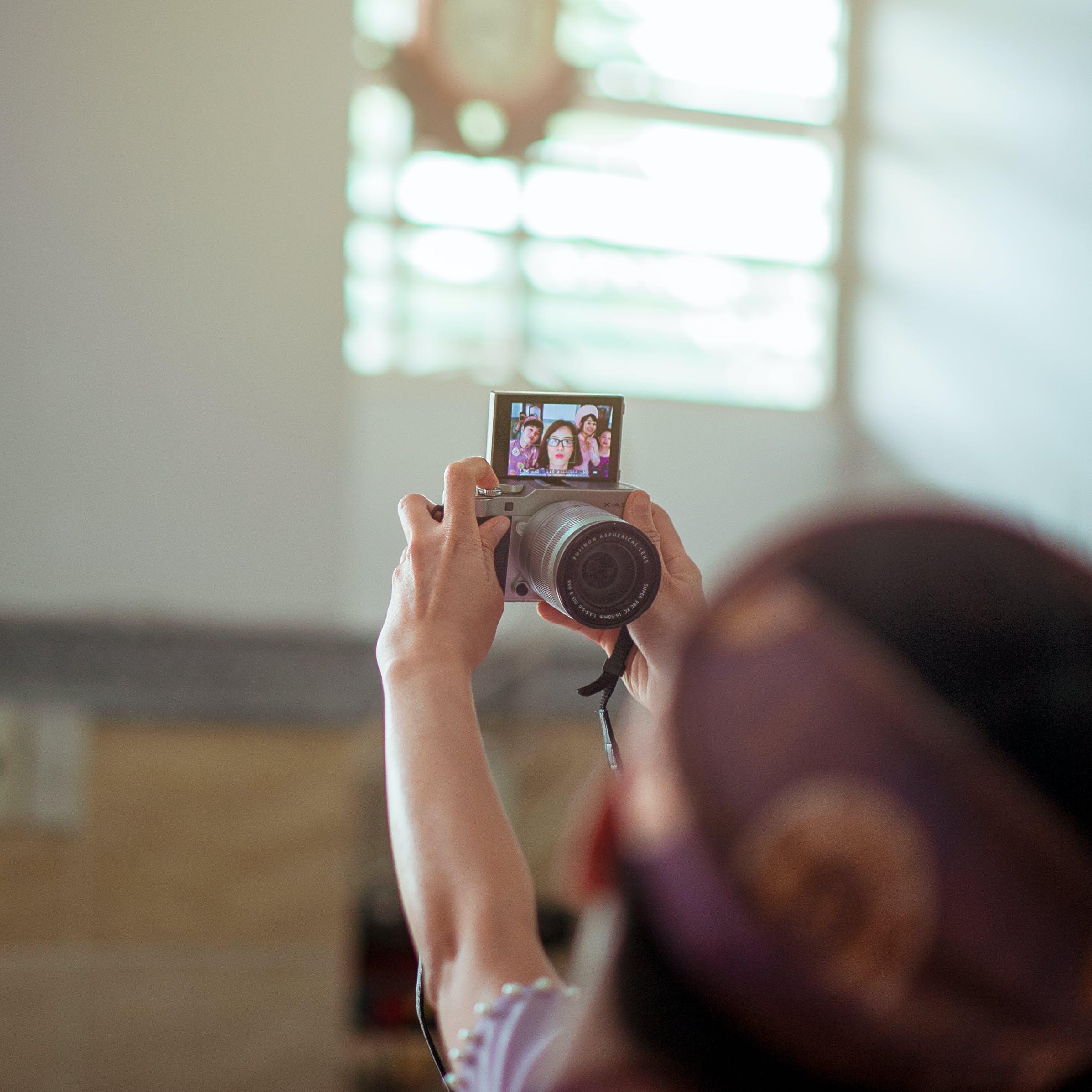 Person Holding Gray Dslr Camera