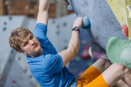 Selective Focus Photo of a Rock Climber in a Blue Shirt