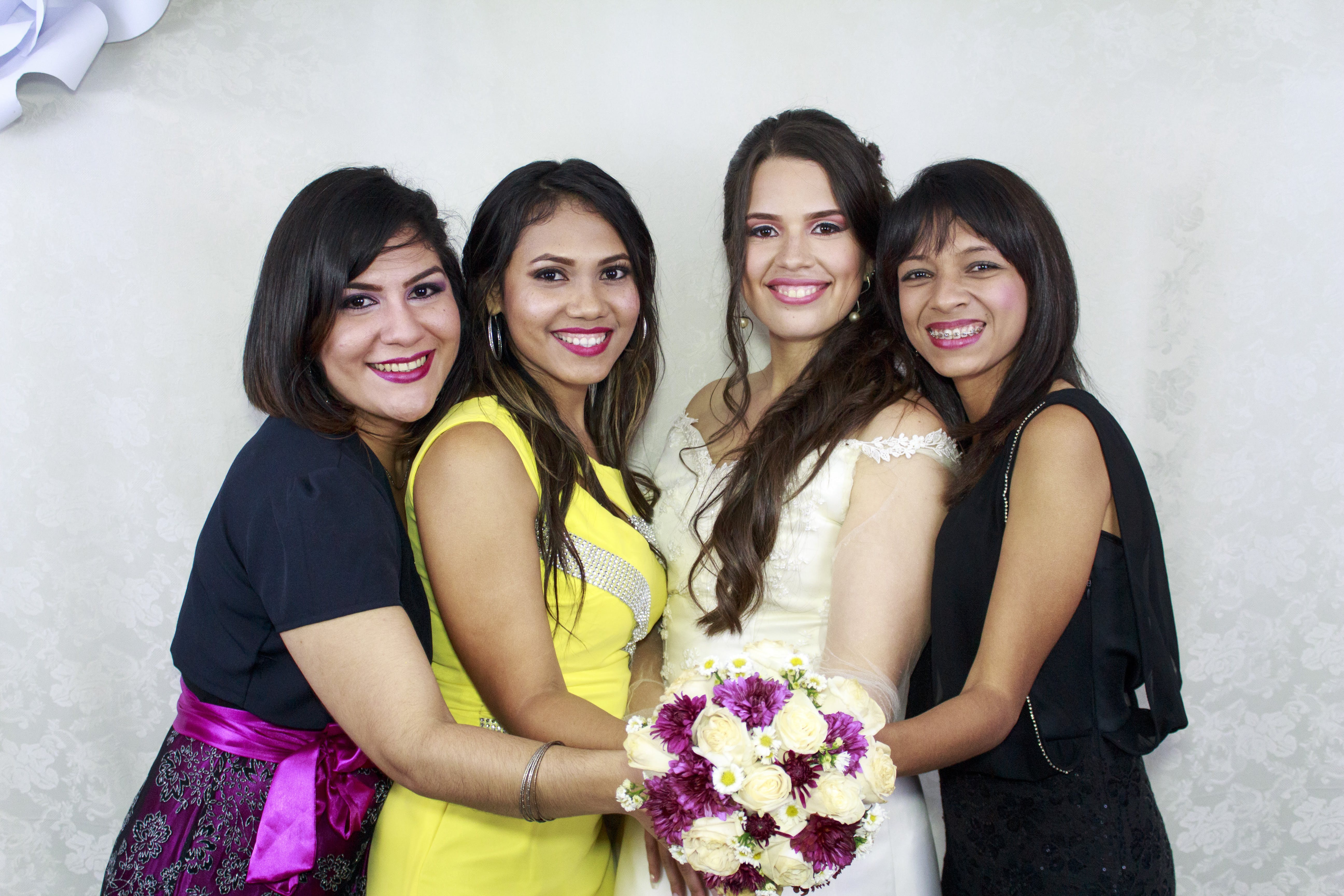 Woman in Beige Wedding Dress Holding Bouquet Flower Together With Other Three Woman in Assorted Colors of Dresses