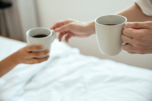 Selective Focus Photo of Two People Holding a Mug of Coffee