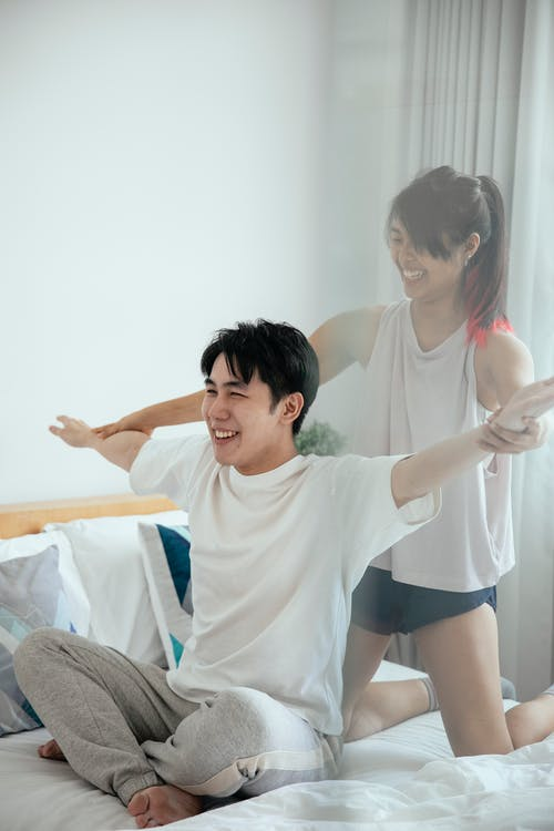 Happy Asian girlifiend helping boyfriend raising hands to sides while practicing morning exercise in bed at home