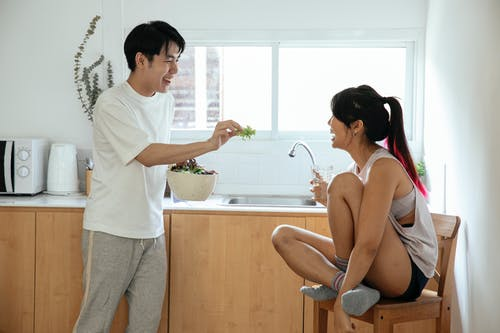 Happy Asian couple in kitchen with salad in bowl