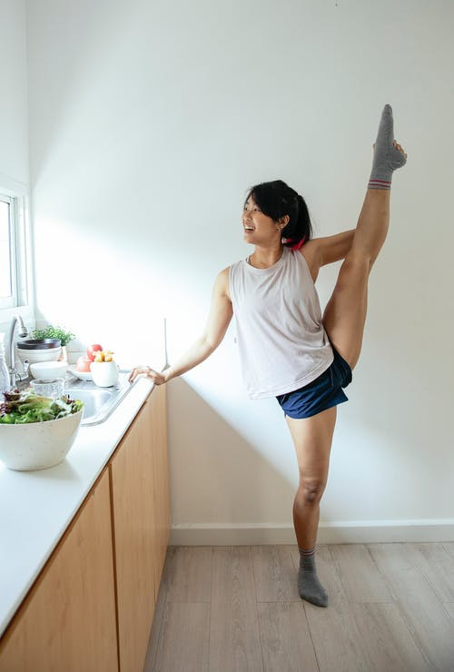 Ethnic lady doing splits near counter in kitchen