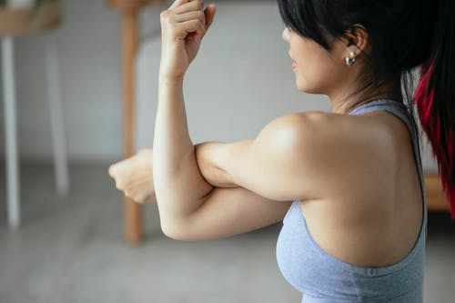 Woman training side arm stretching