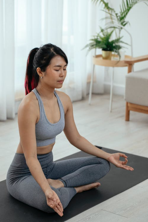 From above of Asian female sitting on mat and meditating in lotus pose while doing yoga at home