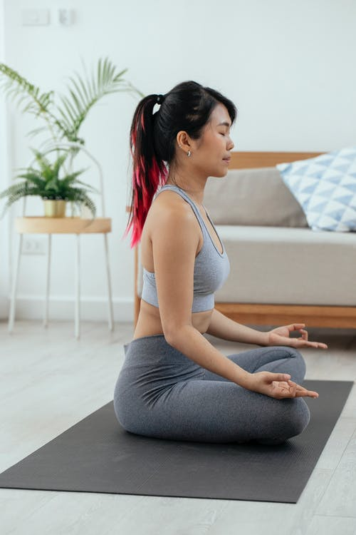 Side view of Asian slim female in sportswear sitting in lotus pose and meditating with closed eyes in living room