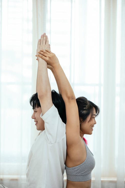 Side view of young Asian female and male in sportswear stretching body while doing acro yoga and standing back to back near window
