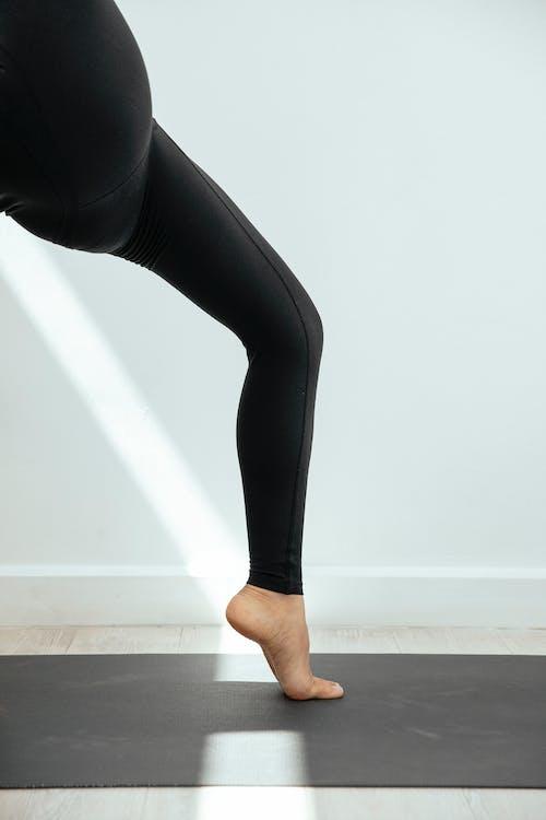 Leg of woman on tiptoe on gray yoga mat