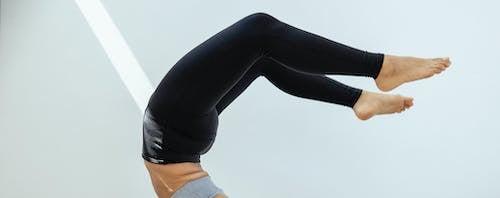 Crop slim woman doing yoga exercise