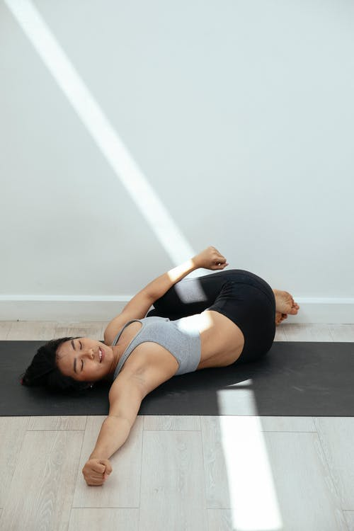 Young slim Asian female wearing top and leggings doing Supine Spinal Twist pose while practicing Supta Matsyendrasana yoga asana on gray mat in light room