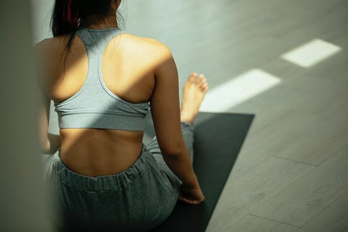 Anonymous barefooted female sitting on mat after yoga session