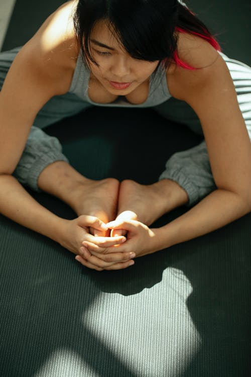 From above of crop focused Asian female with dark hair in sportswear stretching inner thighs while practicing Baddha Konasana A yoga pose on mat