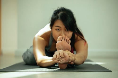 Focused young flexible ethnic female with long dark hair in sportswear stretching leg in Seated Three Limbed Forward Bend and looking at camera