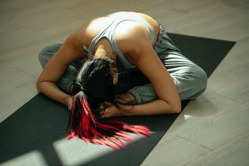 From above full body of anonymous flexible female with long dyed hair bending forward while practicing Baddha Konasana B yoga pose on mat in studio