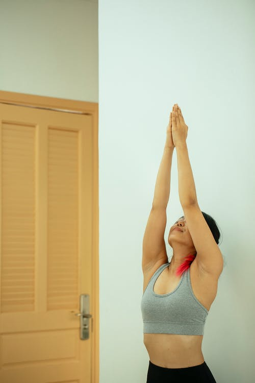 Young fit female in sportswear standing with raised arms while doing yoga near white wall in light apartment