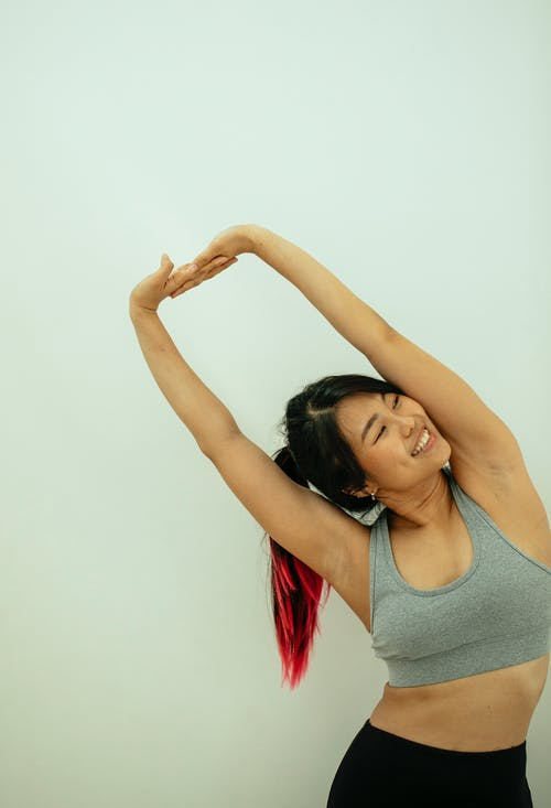 Positive Asian female in activewear stretching arms while practicing yoga and looking away against white wall