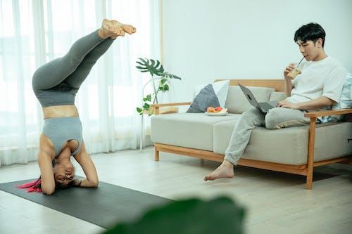 Woman doing handstand on mat