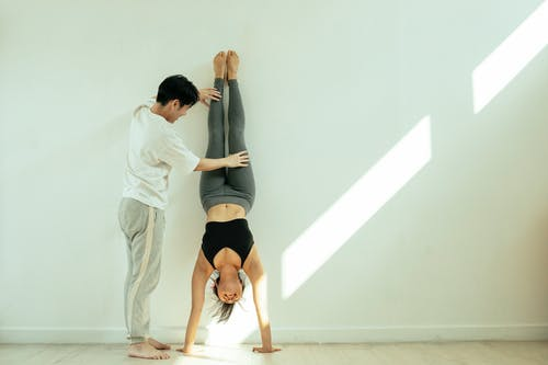 Full body of unrecognizable male instructor helping young female in activewear doing handstand in light room