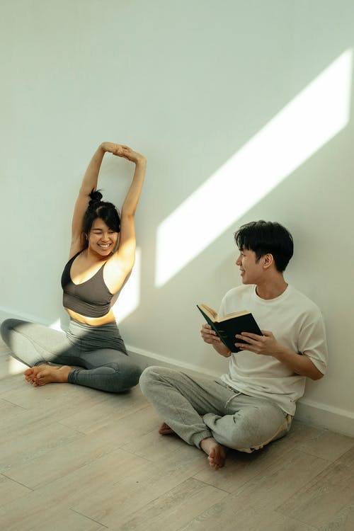 Full body of positive Asian couple in activewear sitting on floor with crossed legs while smiling and looking at each other