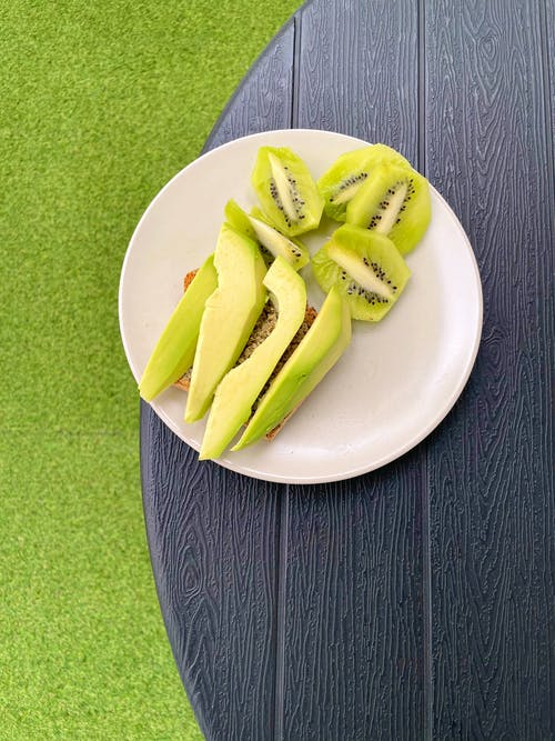 Sliced Green Fruit on White Ceramic Plate