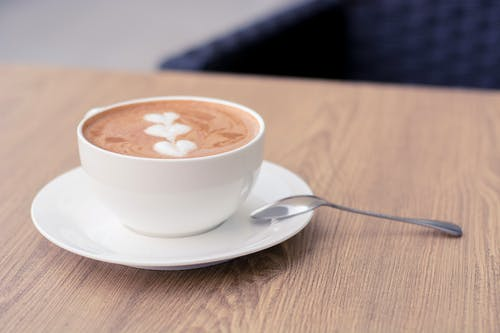 Photo of a Cup of Coffee on a White Saucer with a Metal Spoon
