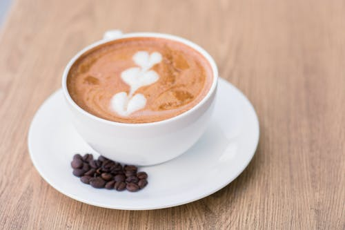 Close-Up Photo of an Espresso Drink with Latte Art Near Coffee Beans