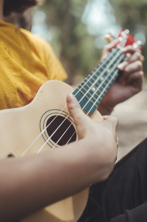 Selective Focus Photo of a Person in a Yellow Shirt Playing the Ukulele