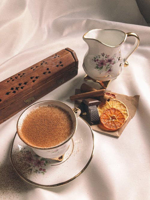 Cup of cacao with aromatic cinnamon near candied fruit