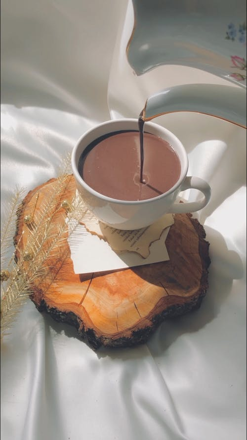 High angle of cocoa pouring from ceramic teapot in cup placed on wooden board on silk fabric