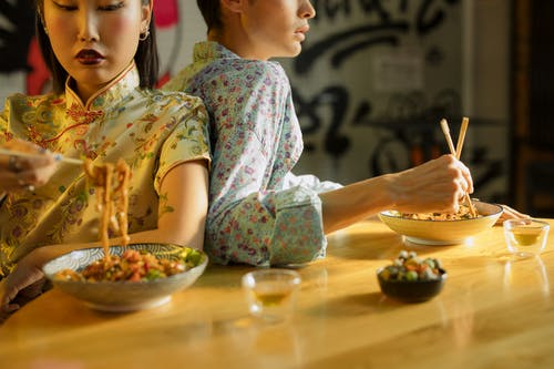 Man and Woman Eating Bowl of Noodles