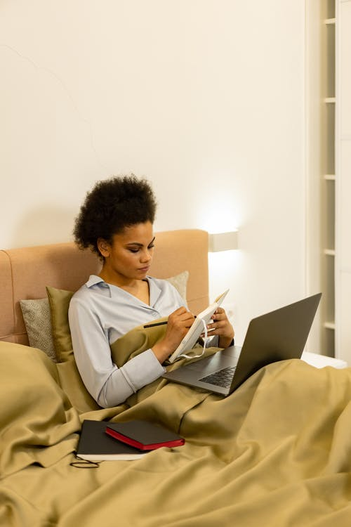 A Woman Writing on a Notebook While Using Laptop