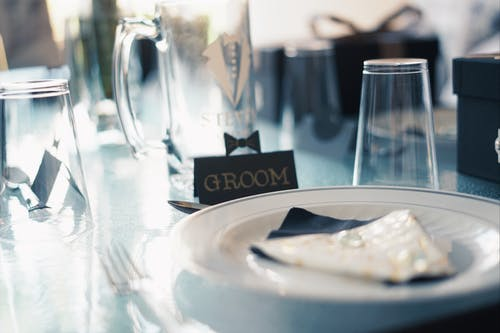 Round White Ceramic Plate Near Glass Cups and Groom Sign