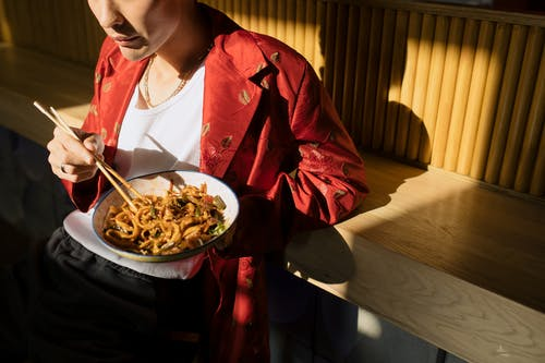 Woman in Red Jacket Eating Pasta