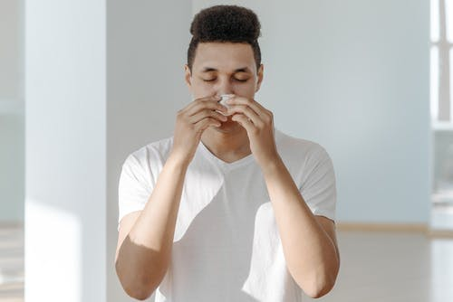 Sick Man in White Shirt Wiping His Nose with Tissue