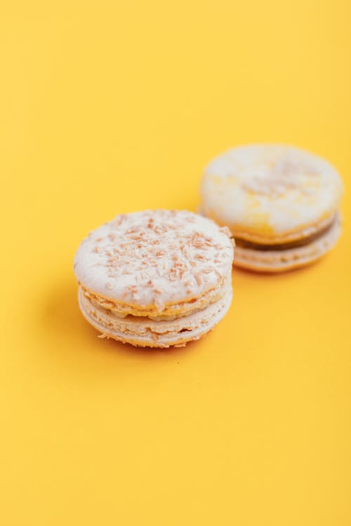 Tasty macaroons placed on yellow surface in daytime
