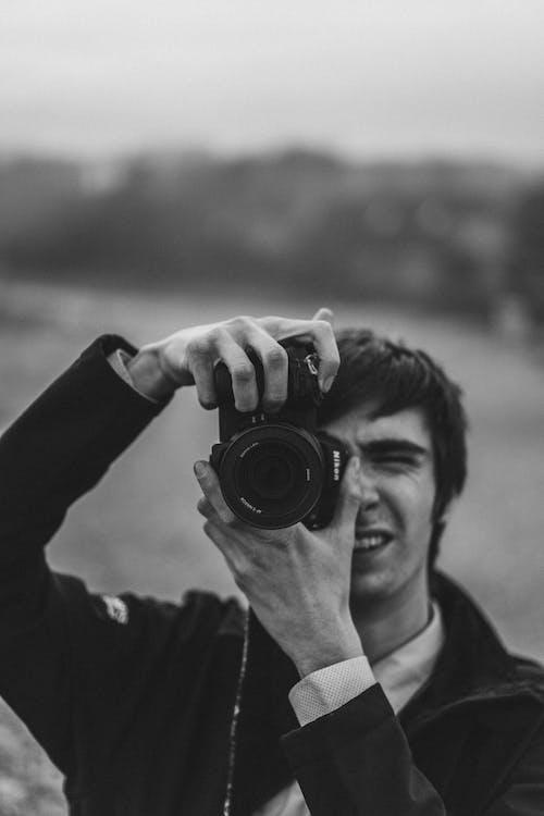 Monochrome Photo of a Man Using a Dslr Camera