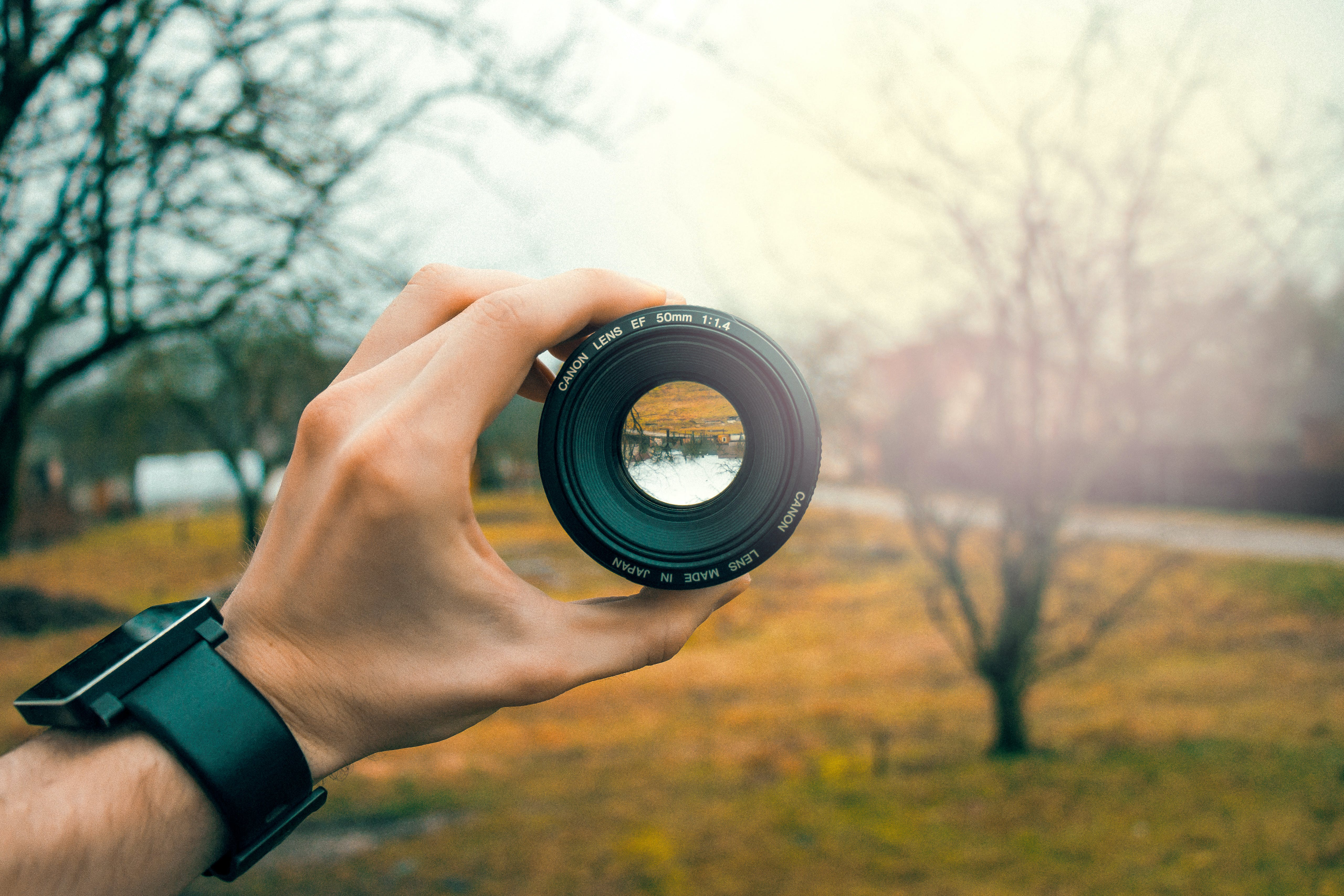 Photography of Person Holding Black Camera Lens