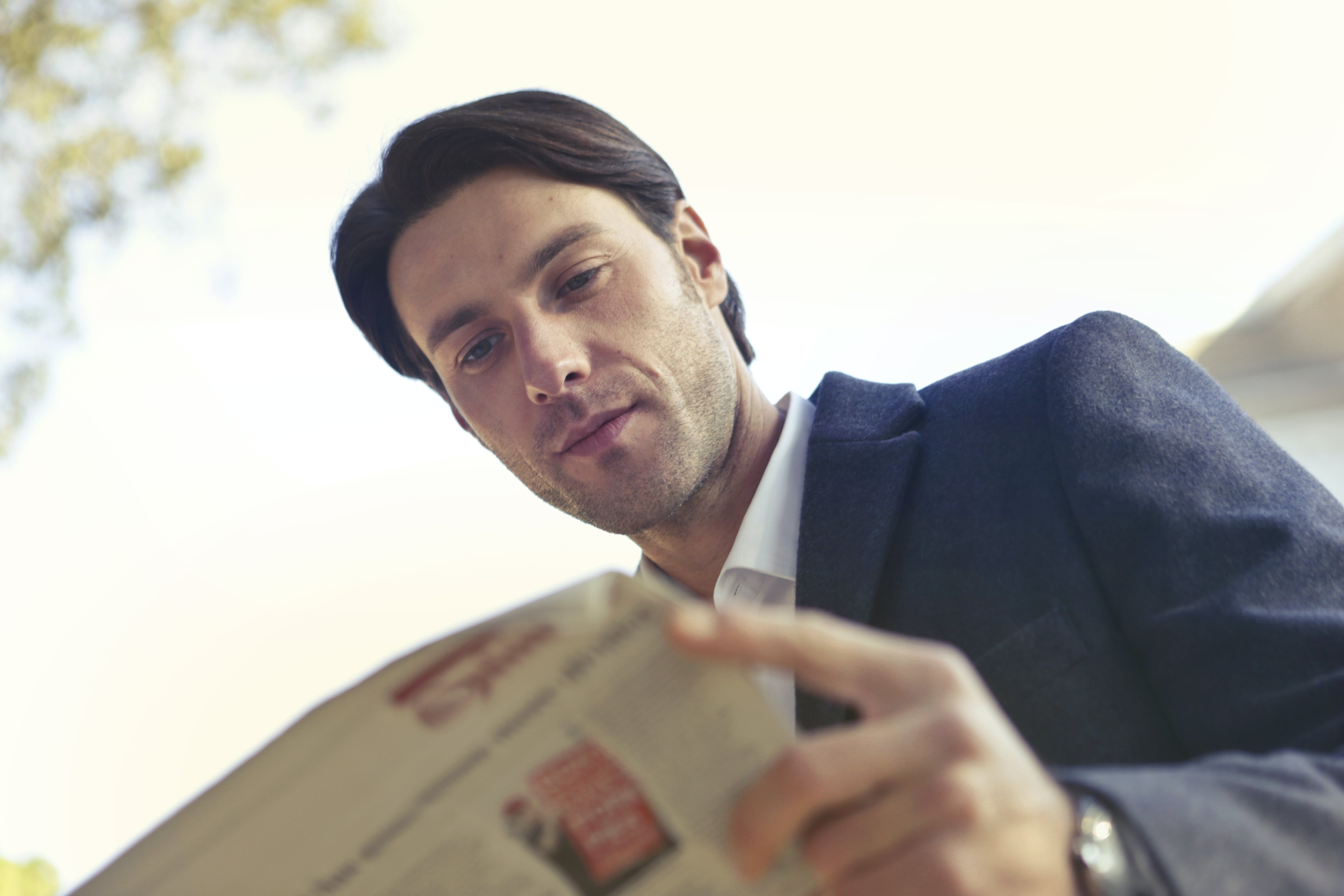 Low Angle Shot of Man Reading Newspaper