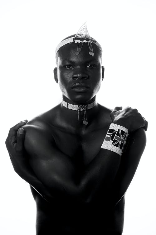 Black man in accessories covering naked torso