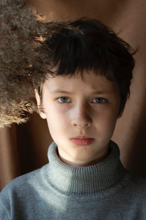 Serious boy near dried plants
