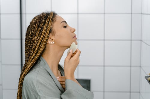 Woman using Gua Sha on her Face