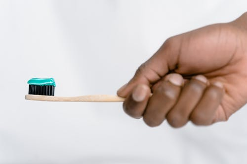 Person Holding Brown Wooden Toothbrush