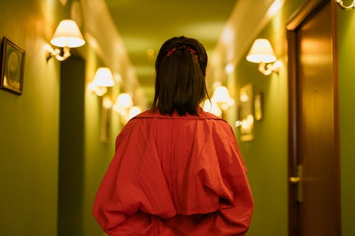 Woman in Red Dress Standing in the Hallway