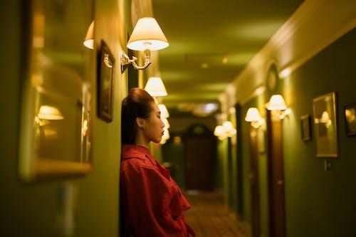 Woman in Red Dress Standing Near Brown Wooden Door