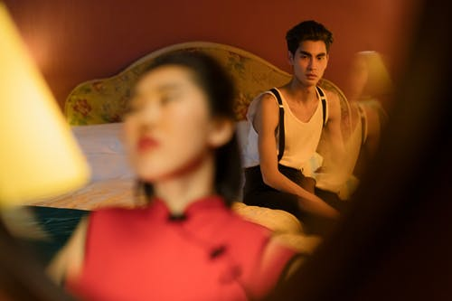 Man Sitting on the Bed Looking at the Woman in Front of the Mirror